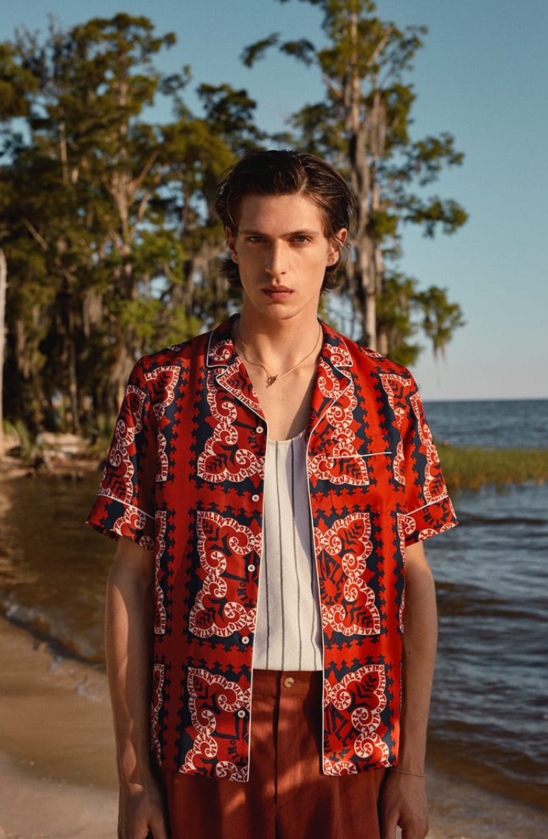 Standing out in red, Edoardo Sebastianelli rocks a Valentino shirt, Marrakshi Life tank, De Bonne Facture shorts, and a Shaun Leane necklace.