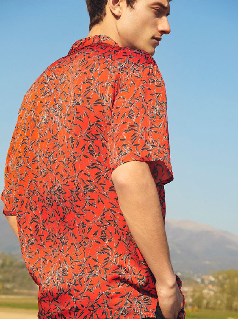Standing out in red, Serge Rigvava dons a printed shirt by Represent.