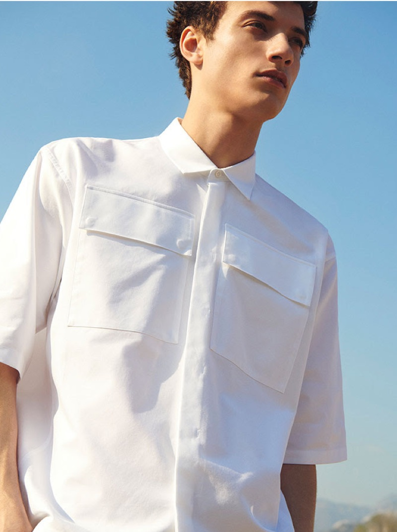 A summer vision, Serge Rigvava sports a white pocketed shirt from YOOX.