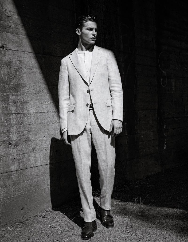 Yulef wears shoes Brooks Brothers, Mantova suit, grandad collar shirt, and woven leather belt Boggi Milano.