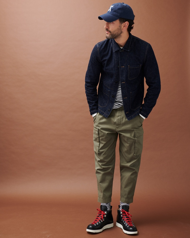Going casual, Noah Mills models a denim jacket with a striped top and cargo pants by Alex Mill.