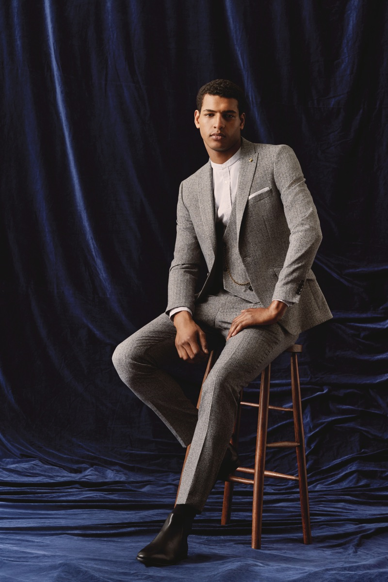 Tidiou M'Baye dons a three-piece grey suit with a band-collar shirt from Burton.