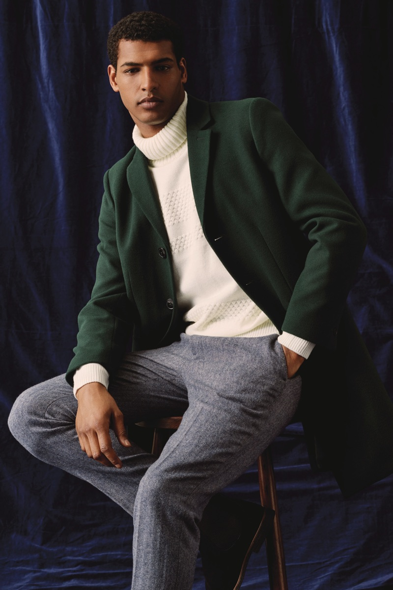 A sleek vision, Tidiou M'Baye wears a green coat with a turtleneck sweater and trousers by Burton.