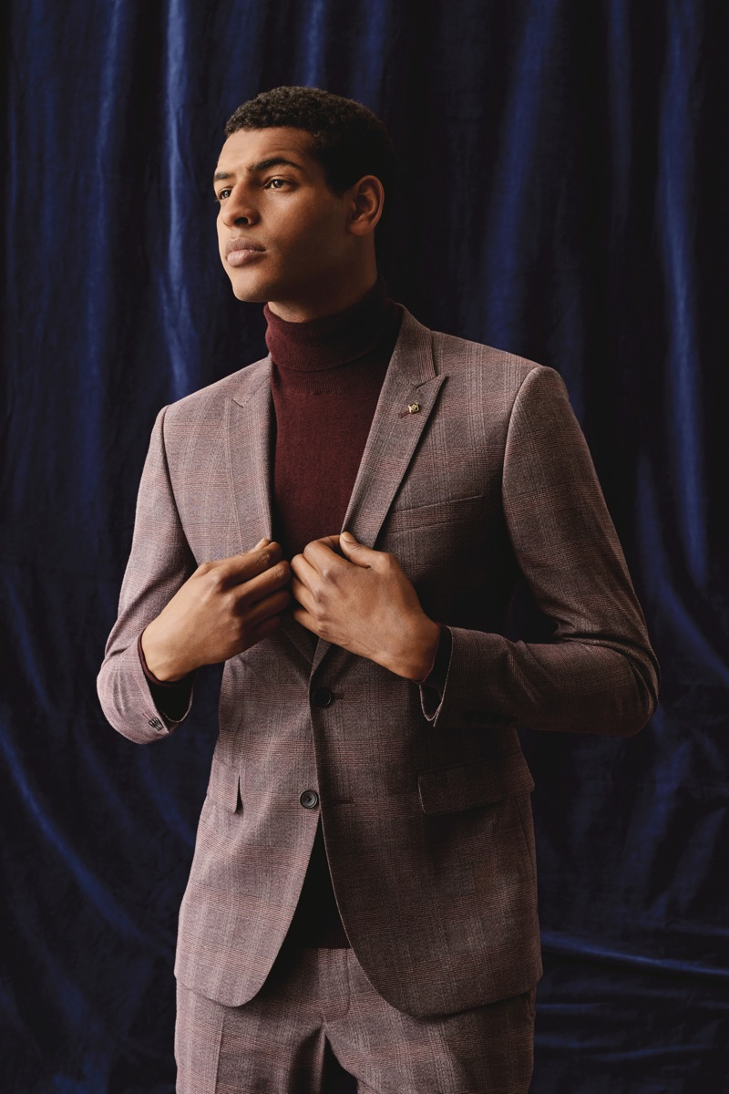 Embracing autumnal hues, Tidiou M'Baye dons a suit and turtleneck sweater from Burton.