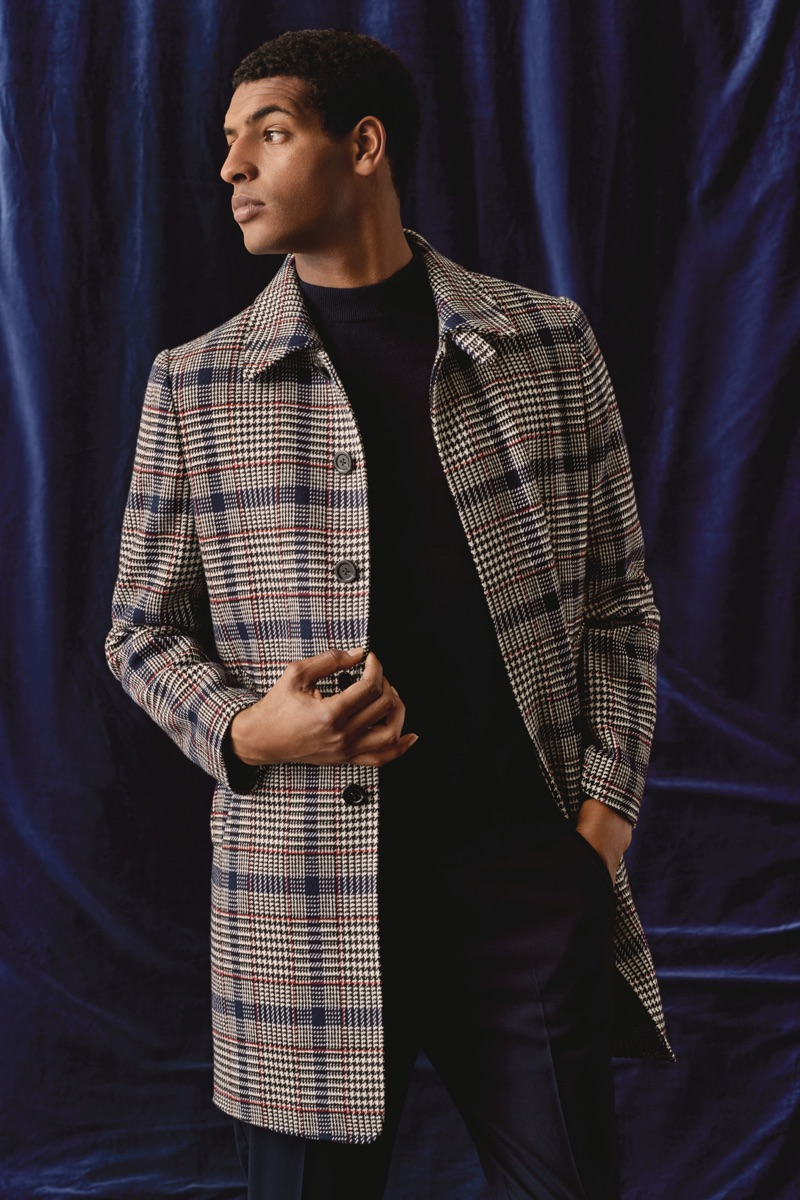 Sporting a checked coat, Tidiou M'Baye wears Burton.