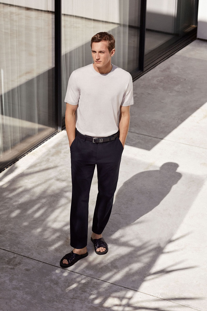 Embracing minimal style, Rutger Schoone wears a white fitted tee with black trousers by COS.
