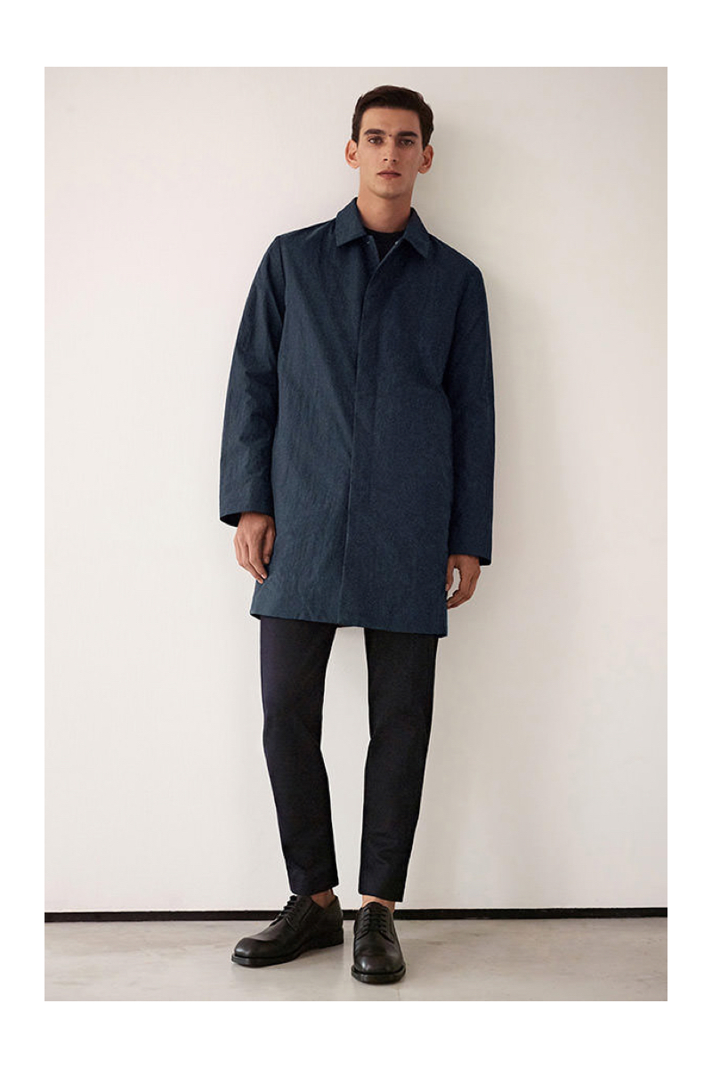 Model Thibaud Charon sports a mac coat with trousers by COS.