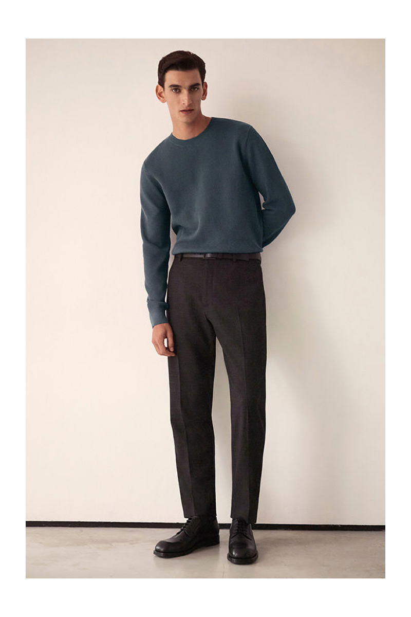 A smart vision, Thibaud Charon wears a fine knit sweater with pleated trousers by COS.