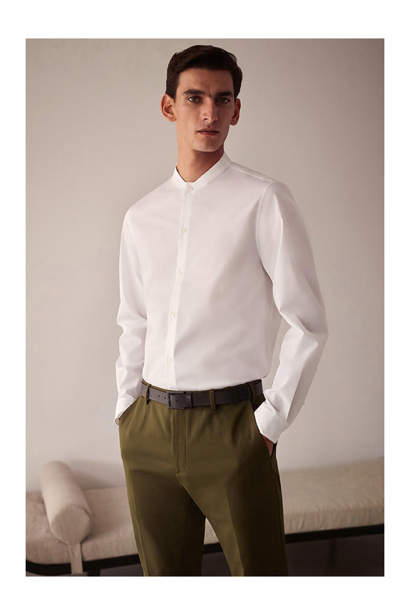 Embracing minimal style, Thibaud Charon models a white band-collar shirt with trousers from COS.
