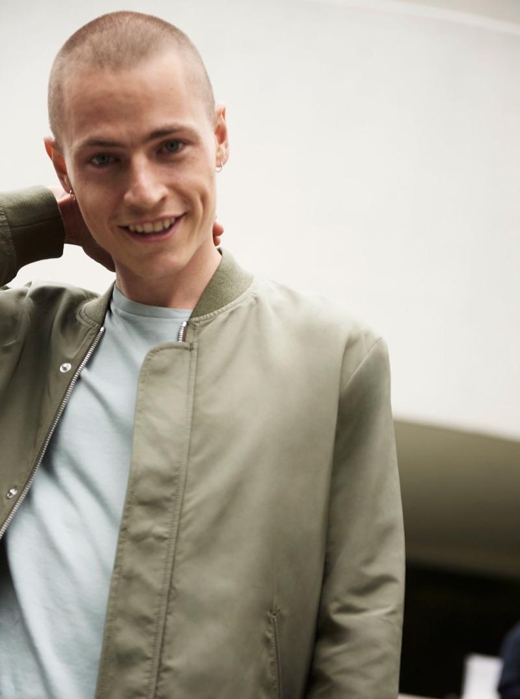 All smiles, Jonas Kloch sports a green bomber jacket by Club Monaco.