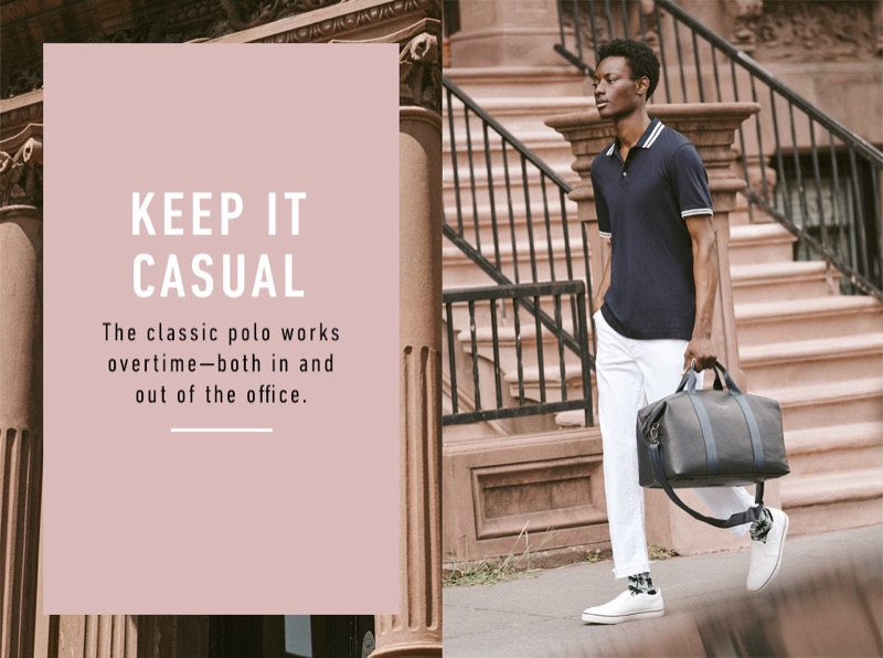 Model Youssouf Bamba dons a Ted Baker polo shirt, duffel bag, and socks with Mother jeans and Vince slip-on sneakers.