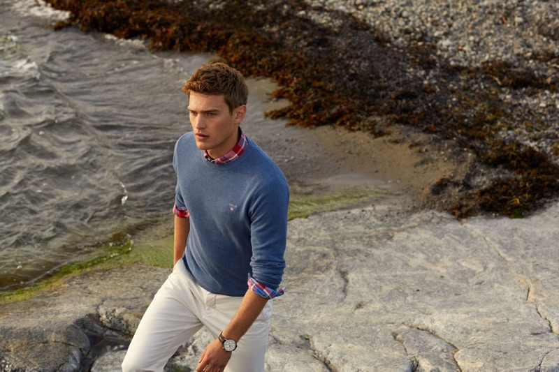 Taking a stroll, Bo Develius dons a sweater with a plaid shirt and chinos by GANT.