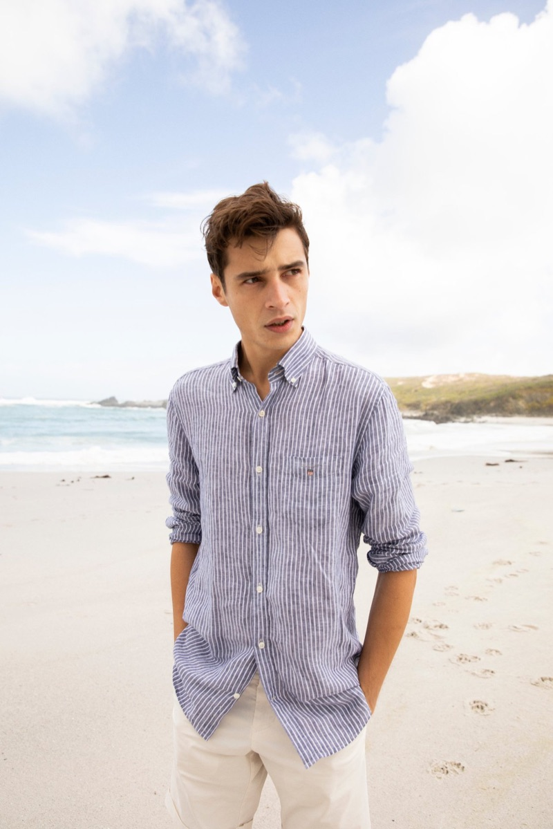 Enjoying a day at the beach, Adrien Sahores dons a striped linen shirt from GANT.