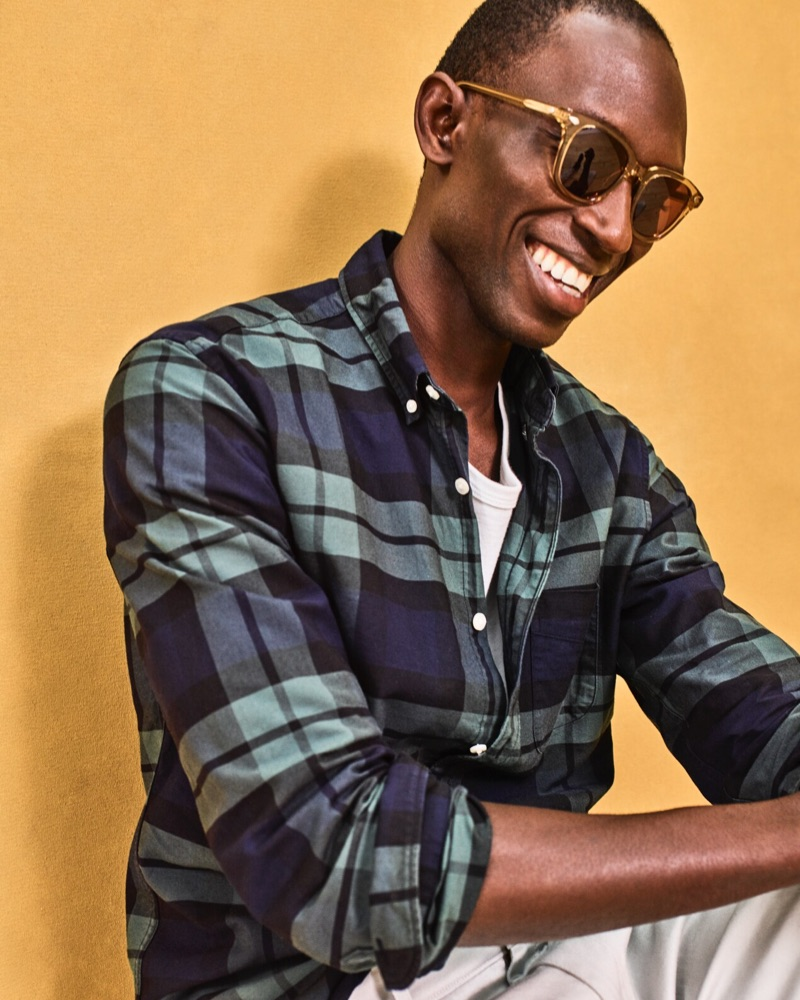 All smiles, Armando Cabral dons a J.Crew plaid oxford shirt $69.50.