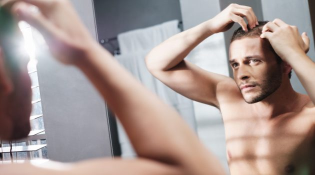 Man Hairloss Looking in Mirror