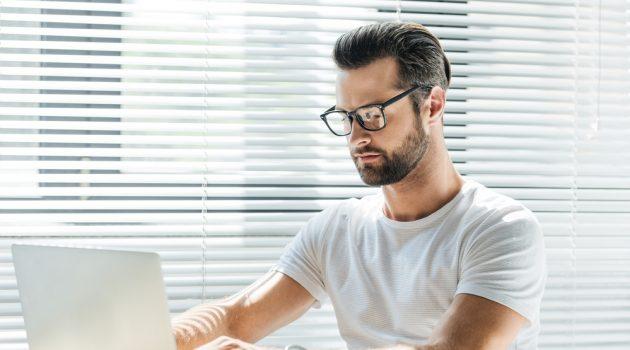 Man on Laptop Wearing Glasses