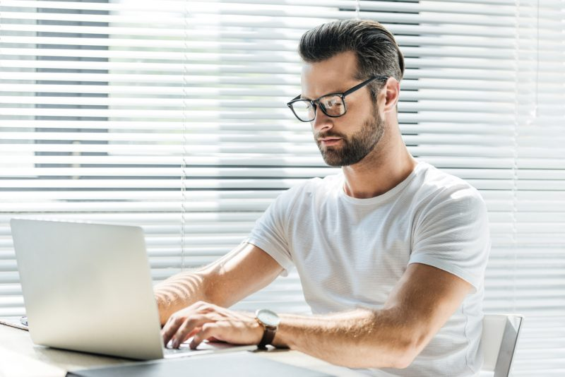 Man on Laptop Wearing Glasses