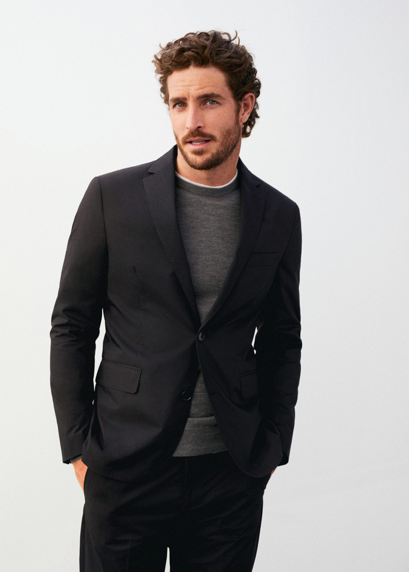 Dressed to impress, Justin Joslin models a two-button suit with a grey sweater by Mango.