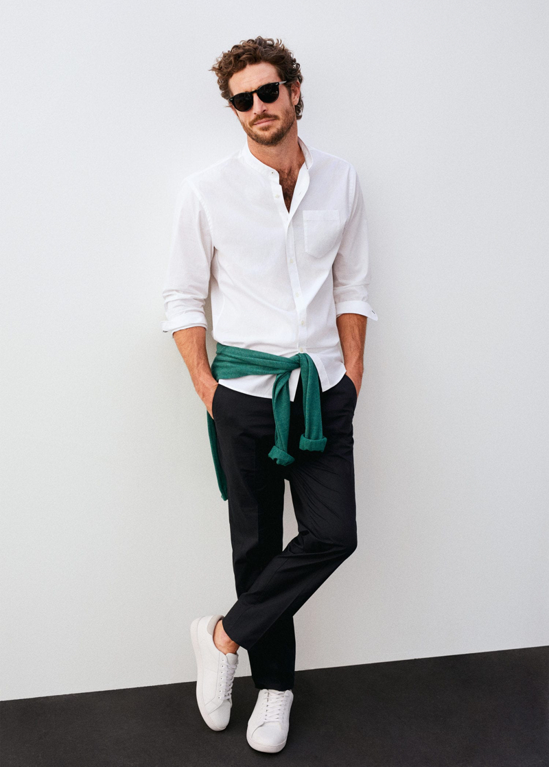 Making a case for smart essentials, Justice Joslin wears a grandad collar shirt with trousers and white sneakers.