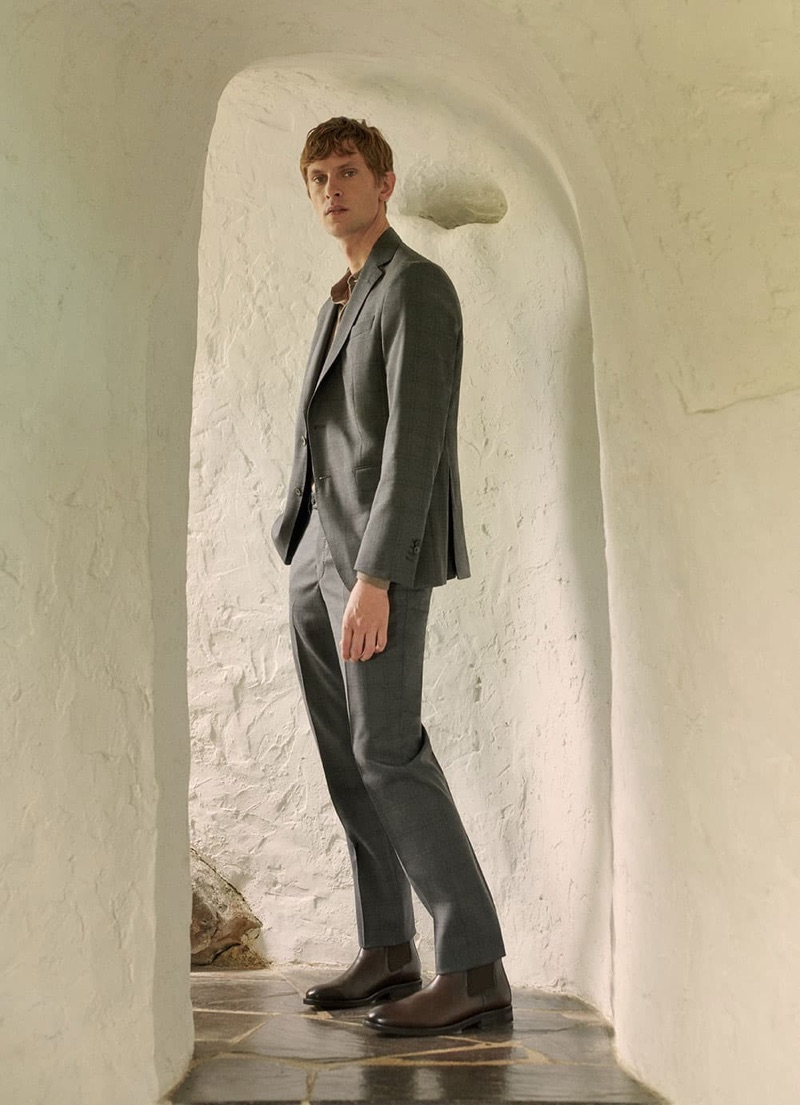 Danish model Mathias Lauridsen sports a grey suit and brown leather boots from Massimo Dutti.