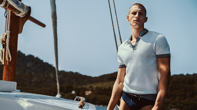 Taking to a sailboat, Augusta Alexander wears a swimsuit and polo from Orlebar Brown.