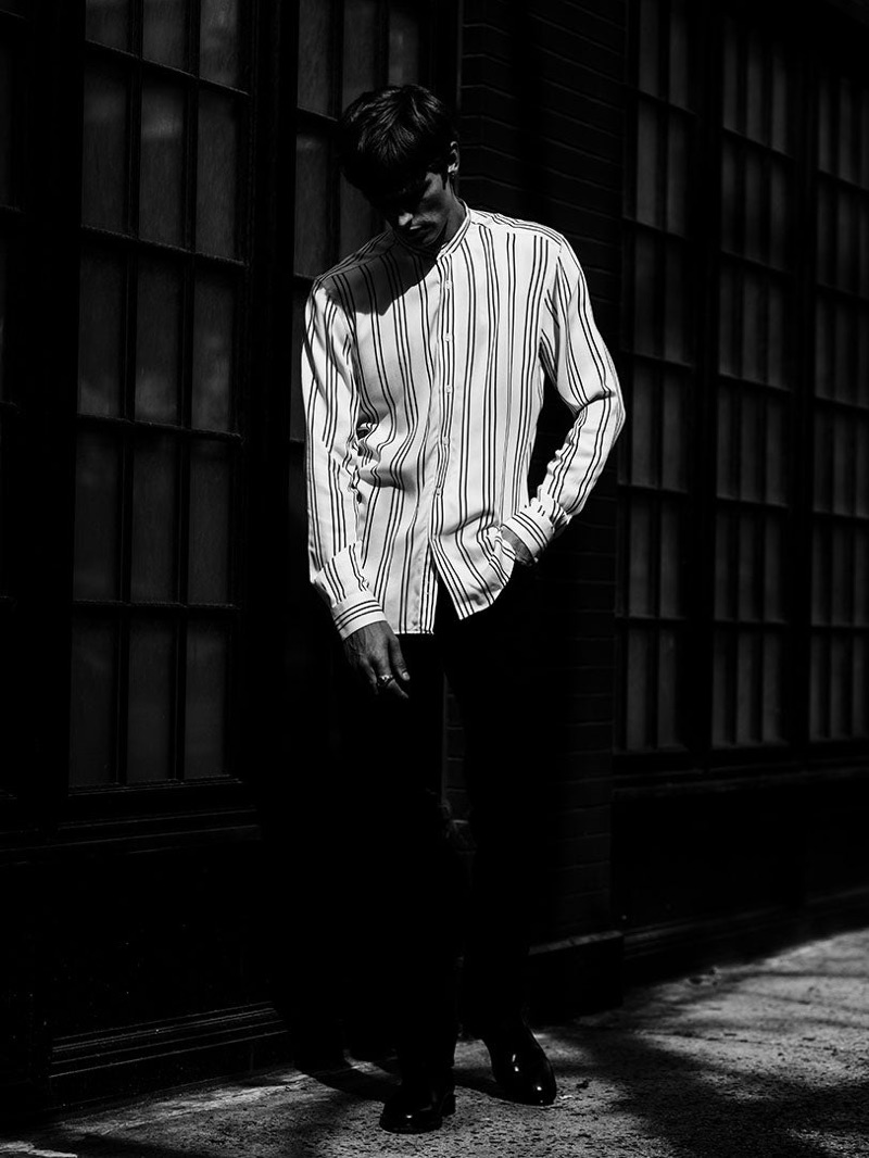 Posing for a moody image, Janis Ancens wears a striped grandad collar shirt by Reiss.