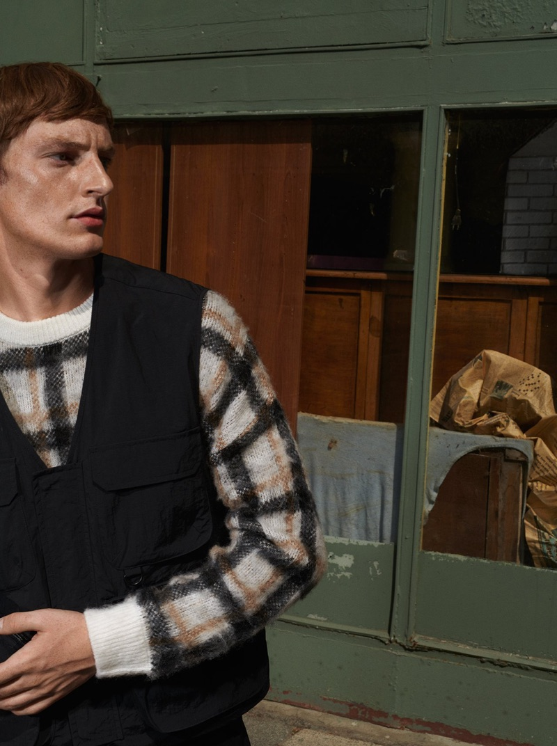 Model Roberto Sipos dons a checked sweater and utility vest from Reserved.