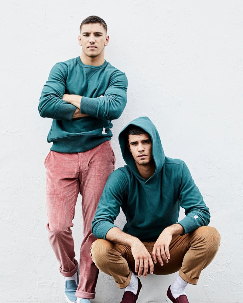 Pictured left, Ismail sports a Todd Snyder + Champion green pullover $148 with Todd Snyder Sutton corduroy trousers $228 in mauve. Meanwhile, Jaad dons a Todd Snyder + Champion green hoodie $138 with corduroy pants.