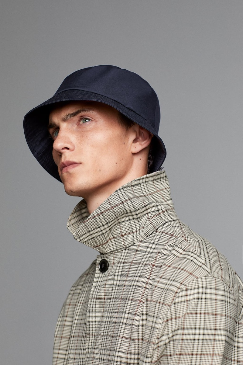 French model Luc Defont-Saviard dons a bucket hat and checked coat from Zara Man's traveler collection.