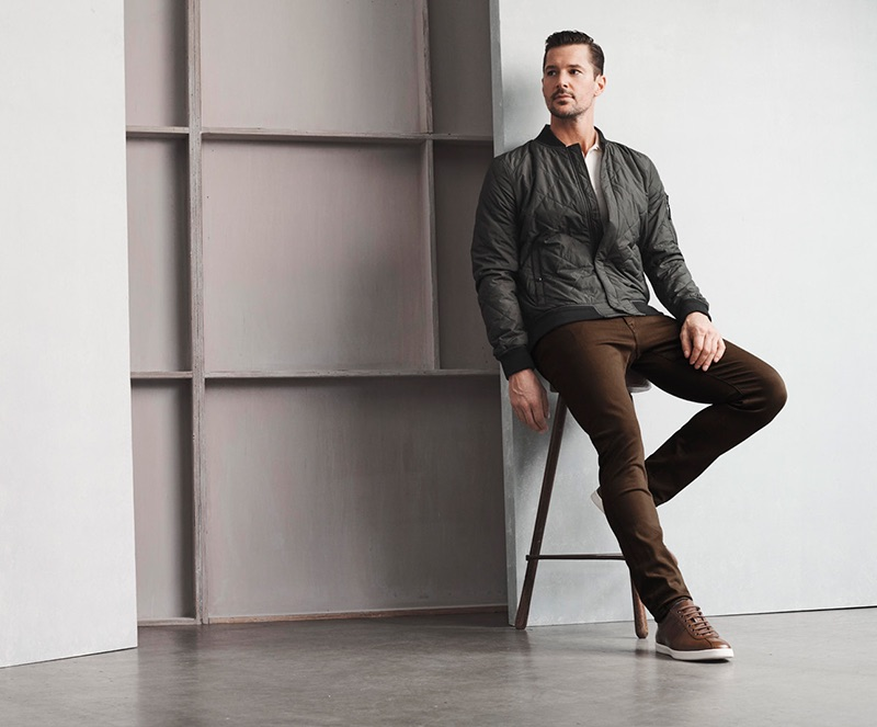 Sitting for a photo, Andrew Shaw models 34 Heritage's Cool mid-rise, slim leg brown pants.