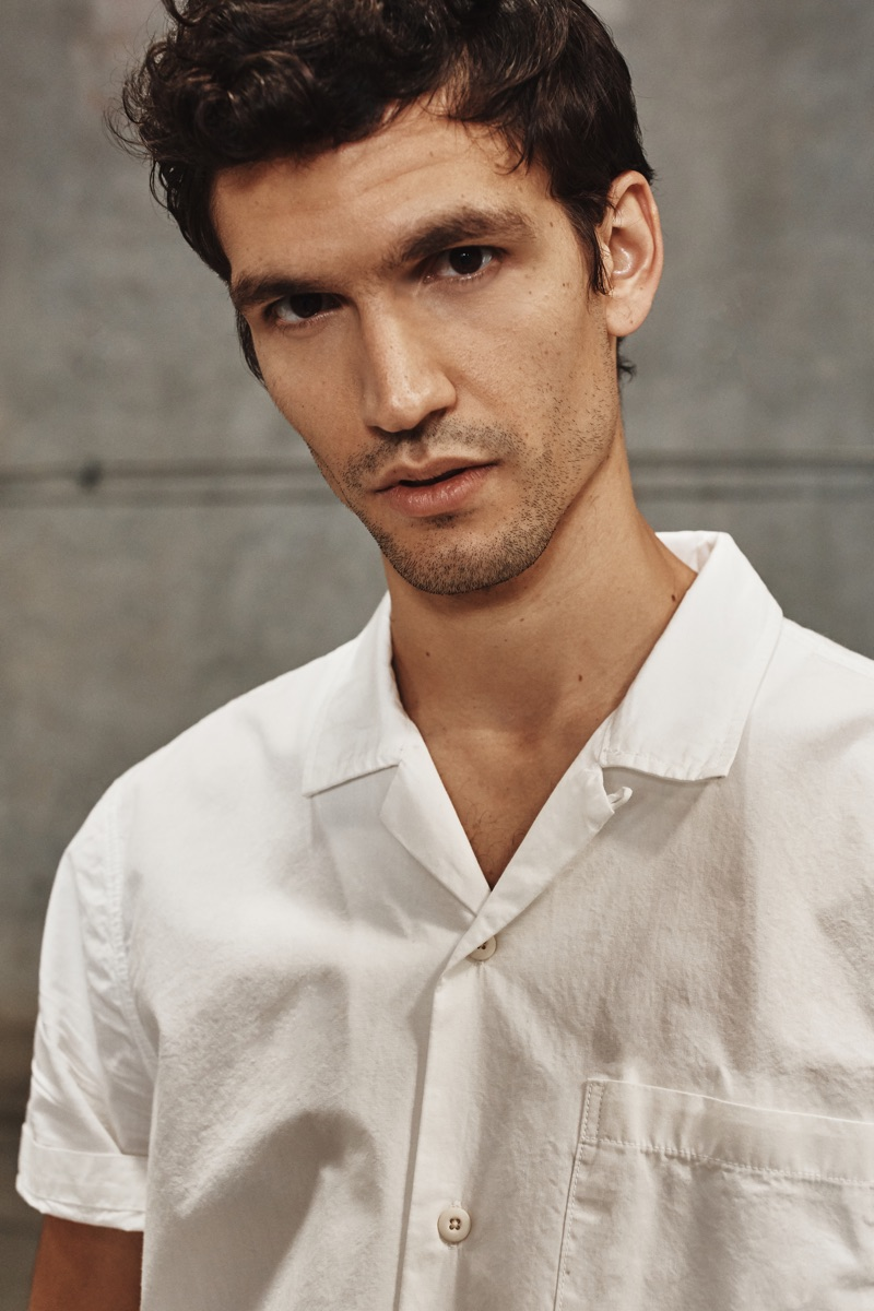 Model Alfredo Nemer rocks a white Cuban-collared shirt from AG Jeans' spring-summer 2020 collection.