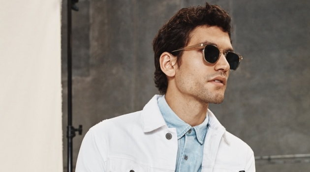 Sporting a white denim jacket and other pieces, Alfredo Nemer wears a look from AG Jeans' spring-summer 2020 collection.