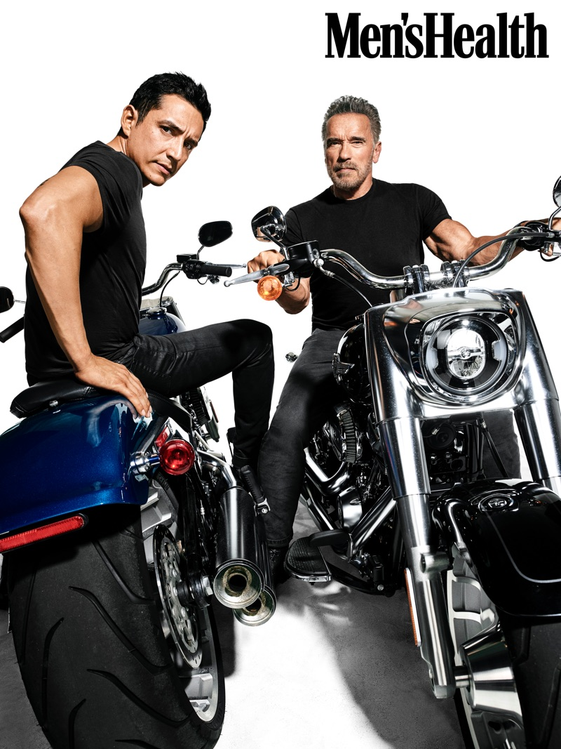 Connecting with Men's Health, Arnold Schwarzenegger and Gabriel Luna pose on motorcycles. Luna wears an Armani Exchange t-shirt with John Varvatos jeans. Schwarzenegger rocks an Armani Exchange t-shirt with jeans and boots by Aether.