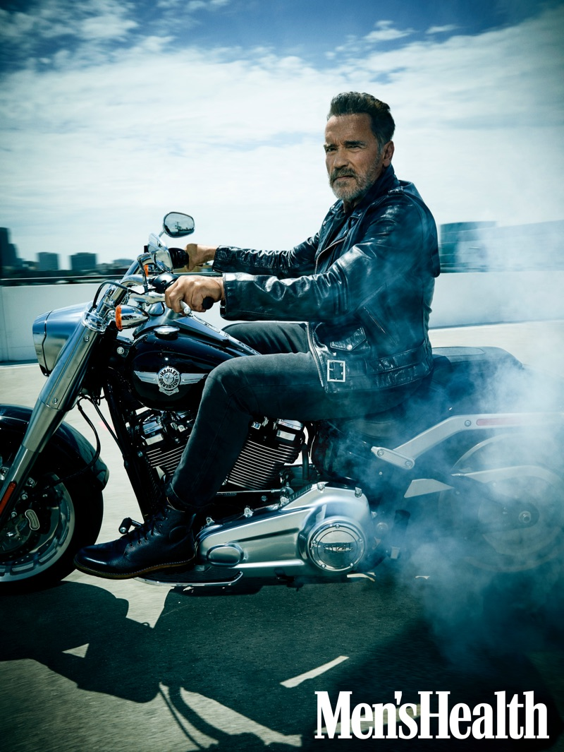 Arnold Schwarzenegger sports a Schott leather biker jacket with jeans and boots by Aether for Men's Health.