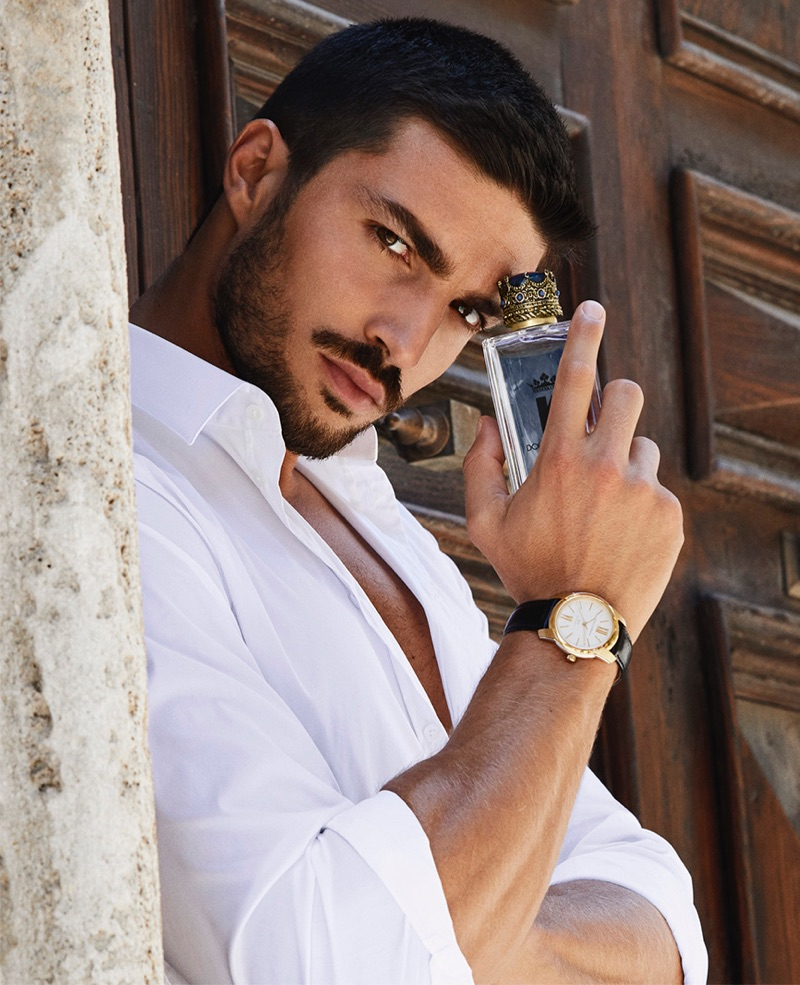 Donning a crisp white shirt, Mariano Di Vaio poses with a bottle of K by Dolce & Gabbana.