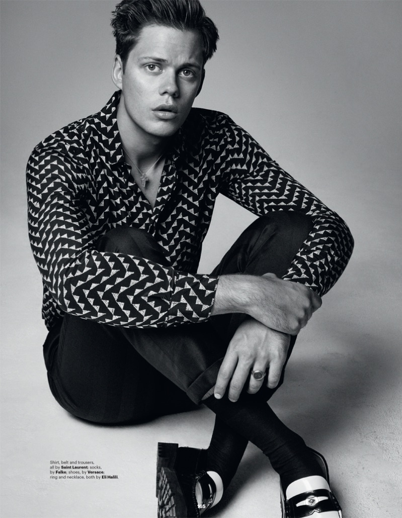Taking to the studio, Bill Skarsgård rocks a shirt, belt and trousers by Saint Laurent. He also dons Versace shoes.