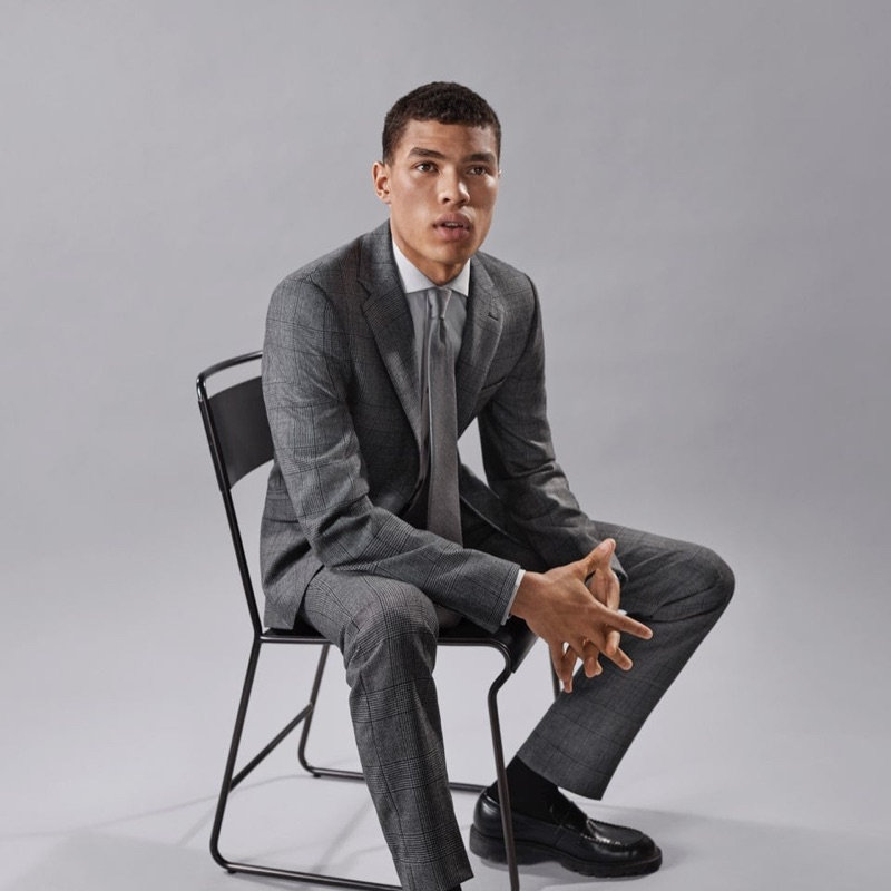 Front and center, Louis Griffiths sports a grey suit by Calvin Klein.