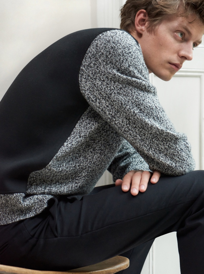 Connecting with Club Monaco, Janis Ancens wears a black and grey mixed material sweater $149.50.
