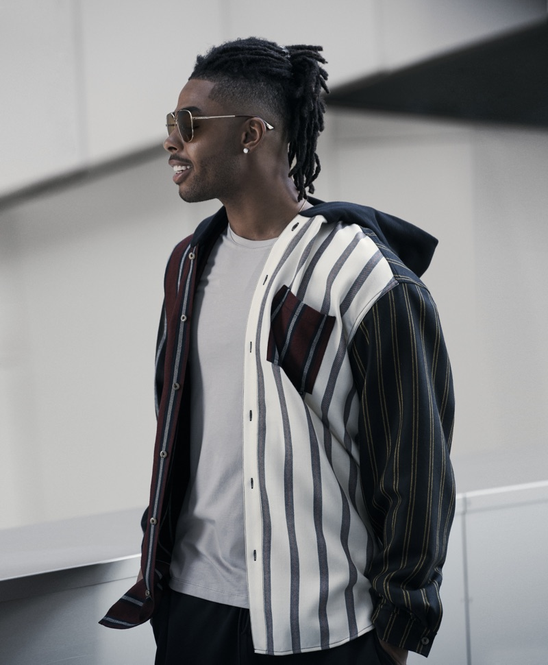 Embracing a subdued color palette, D'Angelo Russell wears an Alexander Wang striped hooded shirt with a Paige t-shirt, Nike sweatpants, and Gucci aviator sunglasses.