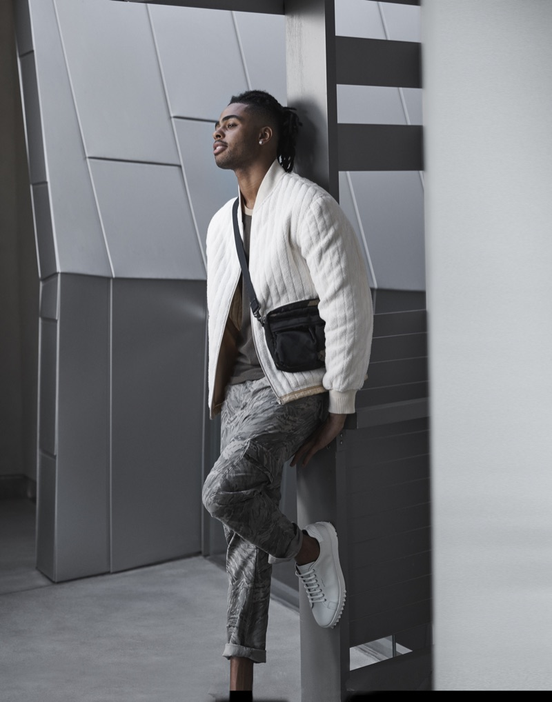 Starring in Bloomingdale's Mix Masters fall 2019 campaign, D'Angelo Russell sports a Helmut Lang fleece bomber jacket and t-shirt. He also rocks J Brand cargo pants in a camouflage print with Salvatore Ferragamo sneakers and a Porter sling bag.