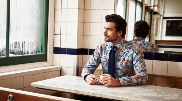 Enjoying a cup of coffee, Paul Kelly models a patterned shirt from Eton's holiday 2019 collection.