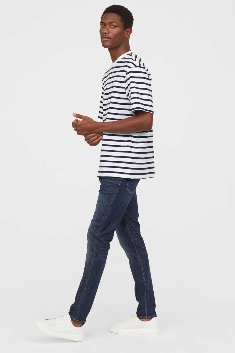 Hamid Onifade models H&M's men's jeans in a slim fit style.