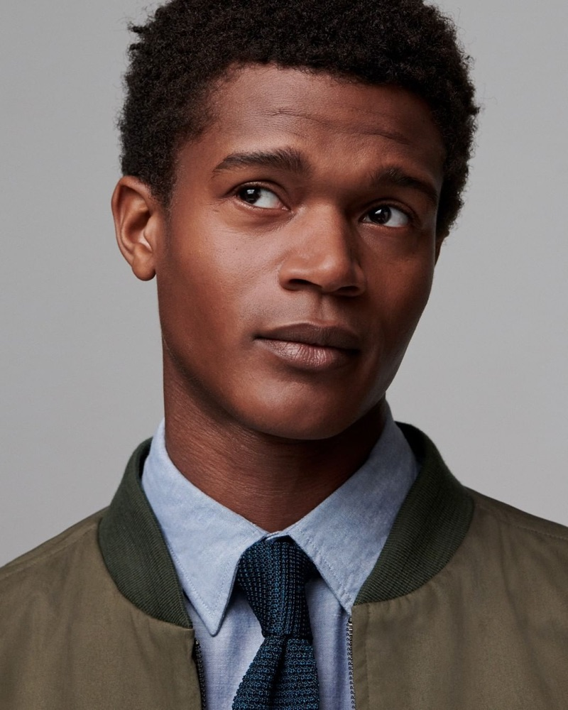 Front and center, O'Shea Robertson models a bomber jacket, shirt, and tie from Jigsaw's fall-winter 2019 men's collection.