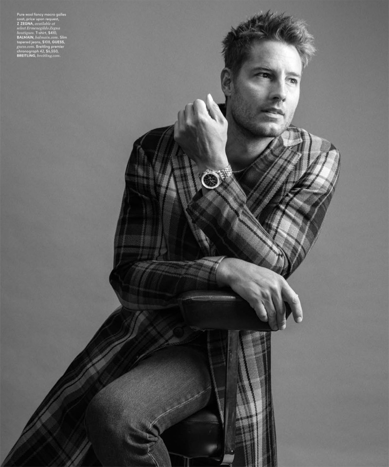 Taking to the studio for DuJour, Justin Hartley wears a checked Z Zegna coat with a Balmain t-shirt, GUESS jeans, and a Breitling watch.