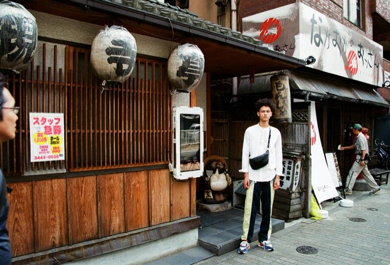 Kai wears shirt Joe Chia, pants Daily Paper, and belt bag Rebecca Minkoff.