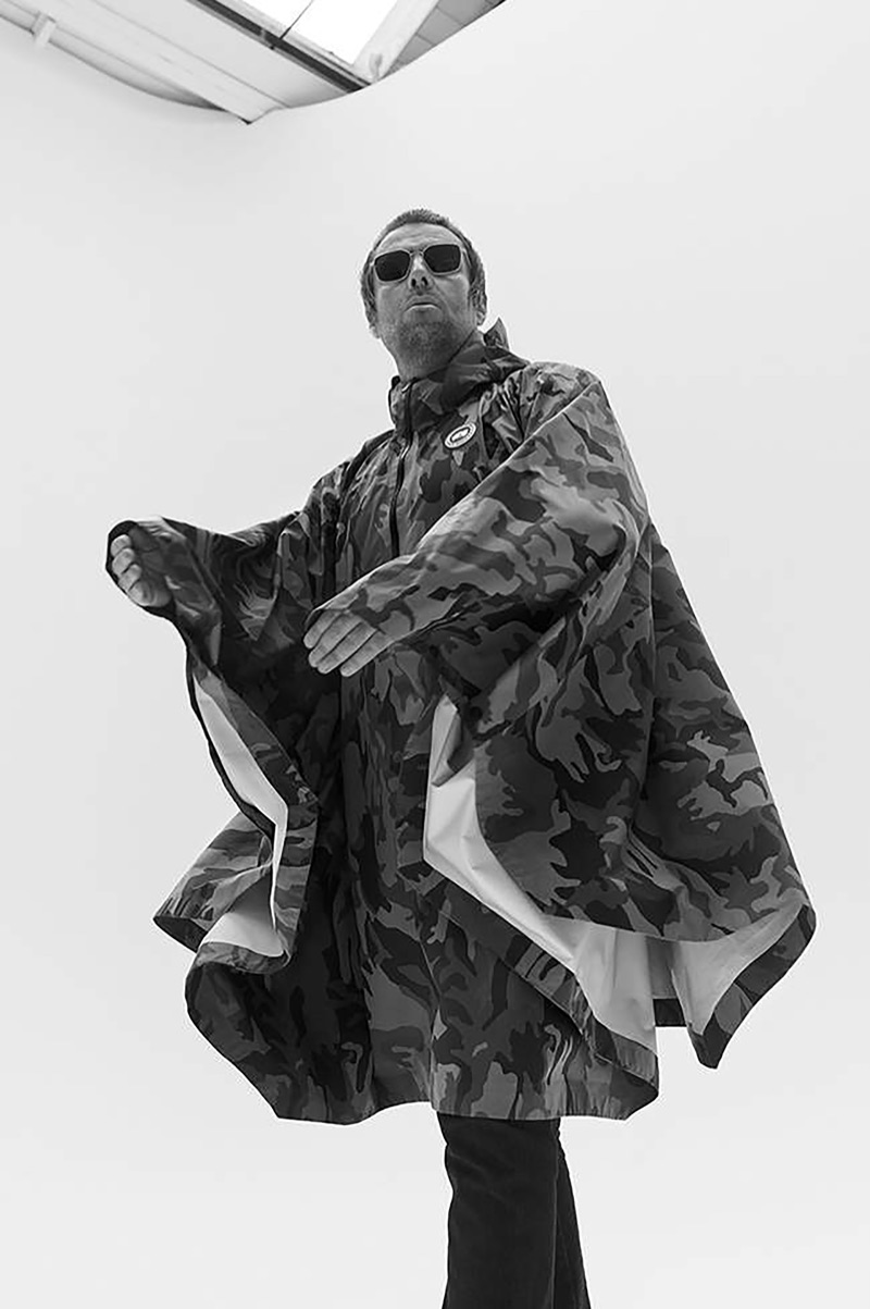 Donning a Canada Goose camouflage print poncho, Liam Gallagher also wears Acne Studios jeans and Cubitts sunglasses.