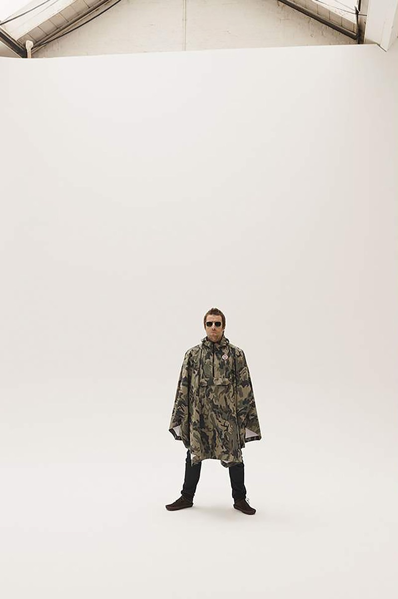 Starring in a photo shoot, Liam Gallagher wears a Canada Goose camouflage-print poncho, Acne Studios jeans, Cubitts sunglasses, and Visvim suede boots.