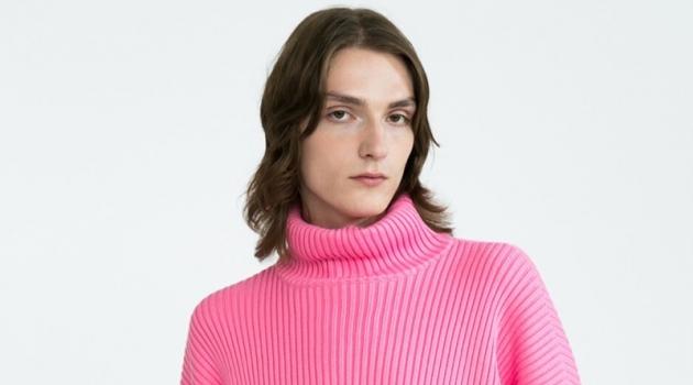 Alex Rychkov sports a pink ribbed Balenciaga turtleneck sweater $1290 and Versace jeans $525.