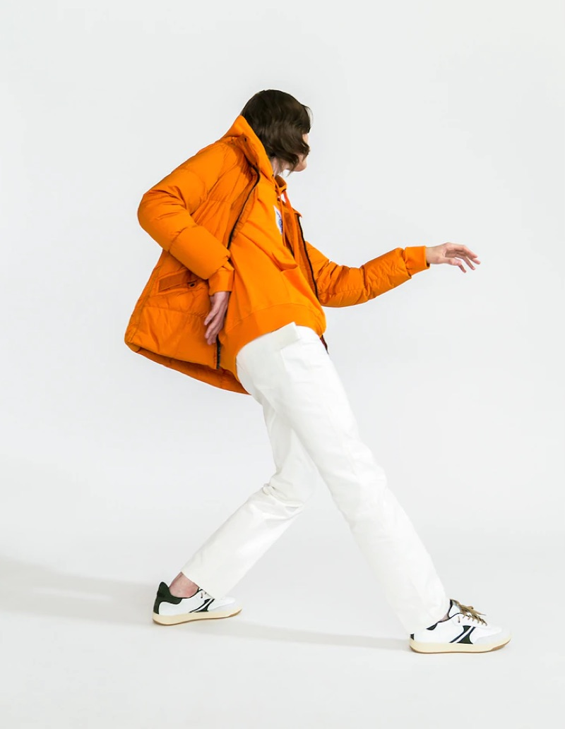Striking a pose, Alex Rychkov dons an orange Stone Island nylon puffer jacket $998, Burberry hoodie $590, white Moncler Genius pants $440, and AM318 sneakers $217.