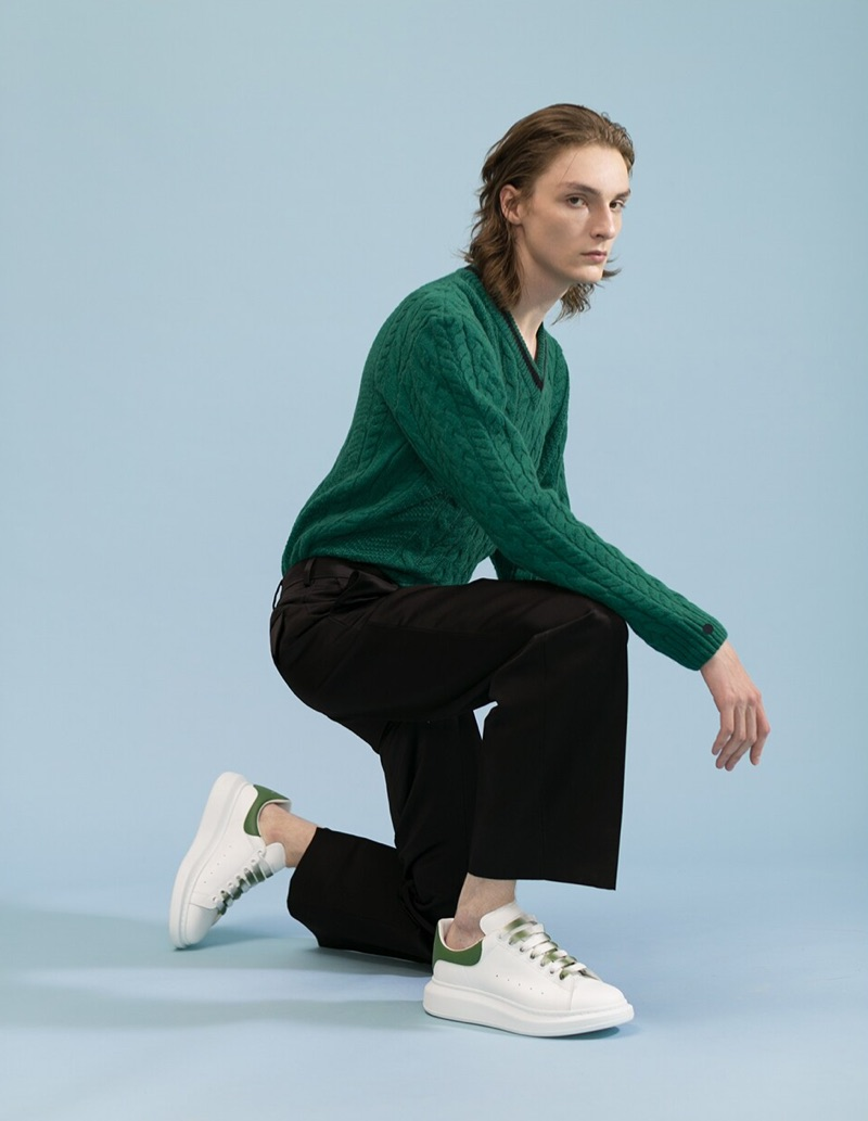 A smart vision, Alex Rychkov rocks a green Lanvin v-neck sweater $1,390, MSGM chino pants $350, and Alexander McQueen sneakers $490.